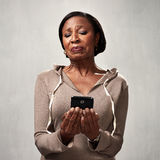 Discontented woman with smartphone. Black mature woman with cellphone disgusted face expression royalty free stock photos