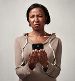 Discontented woman with smartphone. Black mature woman with cellphone disgusted face expression stock photography