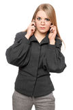 Discontented young blonde in a gray business suit. Portrait of discontented young blonde in a gray business suit with two phones stock images