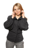 Discontented young blonde in a gray business suit. With two phones stock photos