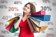 Discontos e conceito da compra A mulher nova e feliz guarda muitos sacos de compras coloridos nas mãos fotografia de stock royalty free