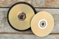 Discos del DVD en viejo fondo de madera fotografía de archivo
