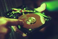 Discos duros del ordenador que son reciclados en el fondo verde Fotografía de archivo