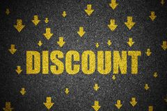 Discount and arrow sign down on asphalt.  Royalty Free Stock Images