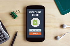 Discount code concept on smart phone screen on wooden desk stock image