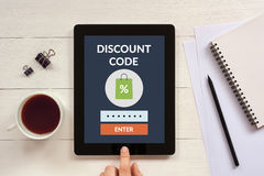 Discount code concept on tablet screen with office objects Stock Image