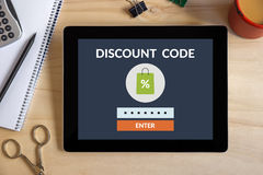 Discount code concept on tablet screen with office objects. On wooden desk. All screen content is designed by me. View from above Royalty Free Stock Photos