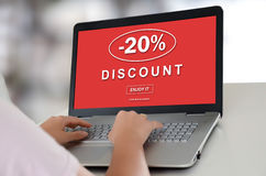 Discount concept on a laptop. Woman using a laptop with discount concept on the screen Royalty Free Stock Image