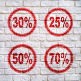 Discount figures for the sale of 25%, 30%, 50%, 70% on the wall, with the effect of cracks. Discounts for sale 25%, 30%, 50%, 70% on a white wall, in red with a Stock Photo