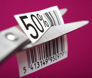 Discount of half price. Scissors cuts the barcode, discount of half price Royalty Free Stock Images