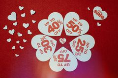 Discount promotion sale. Five big white hearts with per cent numbers surrounded by other small hearts. Over the red background stock photos
