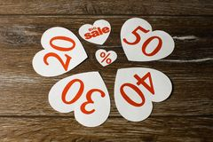 Discount promotion sale. Four big white hearts with per cent numbers and smaller one for big sale over wooden background. Close up stock photo