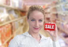 Discount Sale Shopper Woman with Card. A woman is holding up a red card that has the word SALE on it. She looks happy and is standing in a department store Royalty Free Stock Photography