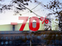 Discount seventy percent 1. The red announcement of a seventy-percentage discount on a glass show-window. The city street is reflected in glass Royalty Free Stock Photos