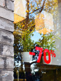 Discount seventy percent 2. The red announcement of a seventy-percentage discount at a window of cafe in the brick building. The blue sky and trees with  yellow Royalty Free Stock Photo