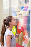 Discount showcase. Portrait of attractive girl is loking on clothes showcase with discount labels Royalty Free Stock Photography