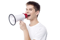 Discounted sale start from today !. Young man proclaiming into megaphone Stock Images