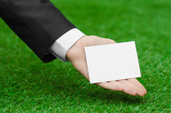 Discounts and business topic: hand in a black suit holding a white blank card on green grass background Royalty Free Stock Photos
