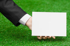 Discounts and business topic: hand in a black suit holding a white blank card on green grass background Stock Photos