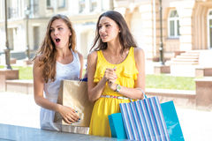 Discounts at the outlet store. Girls holding shopping bags and s Royalty Free Stock Image