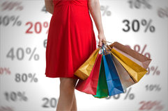 Discounts and shopping concept. Young woman holds many colorful shopping bags in hands.  royalty free stock photography