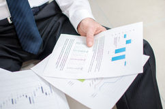 Discouraged businessman sitting on the floor. With graphs in his hands Stock Photos