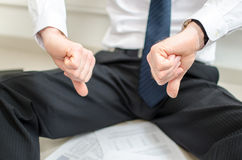 Discouraged businessman sitting on the floor. With thumbs down Stock Photo