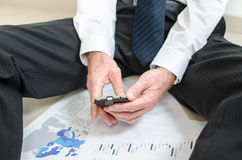 Discouraged businessman sitting on the floor. Using his smartphone Stock Photo