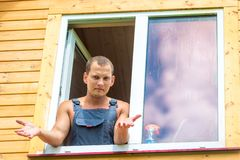 Discouraged man in overalls reflects on washing the window. In the house stock image