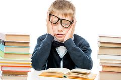 Discouraged schoolboy among a pile of books on a white backgroun. D Royalty Free Stock Image