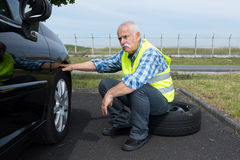 Discouraged senior man attempting to change tyre. Discouraged senior man attempting to change a tyre Stock Images