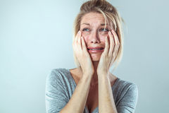 Discouraged young blond woman in pain expressing her sadness. Drama concept - discouraged young blond woman in pain with big tears expressing her disappointment Stock Photo