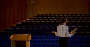 Discours de pratique de jeune femme d'affaires caucasienne dans l'amphith??tre vide 4k banque de vidéos