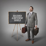 Discover a different world text on blackboard with businessman Royalty Free Stock Photography