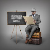 Discover a different world text on blackboard with explorer businessman Stock Photos
