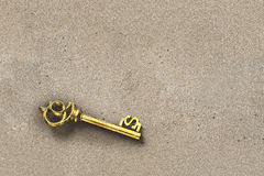 Discover gold treasure key in dollar shape inside dirty sand nob Royalty Free Stock Image