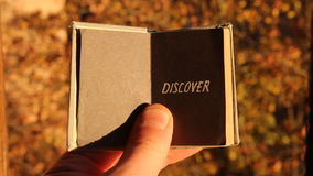 Discover, vacation or travel idea. Hand holding a book with text Discover stock video footage