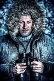 Discoverer. Handsome brutal man dressed in winter clothes covered with frost looking through binoculars Stock Photography