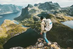 Discoverer man standing on cliff mountain in Norway. Traveling lifestyle adventure concept hiking active summer vacations outdoor aerial view royalty free stock image