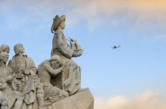 Discoverer's Monument, Lisbon, Portugal. In the background a airplane flying in the blue sky at the statue Royalty Free Stock Images