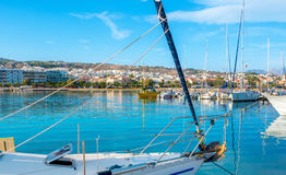Discovering the coast of Rethymno. The view through the sails and ropes of the yacht on the coastline of the modern tourist districts of Rethymno, Crete, Greece stock images