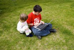 Discovering laptop. Boy and the girl with the laptop,in the garden Stock Photos