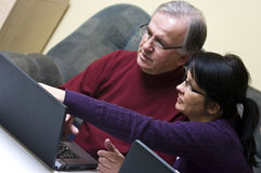 Discovering laptop. A woman (daughter) teaching a senior man (father) how to use a laptop Royalty Free Stock Photography