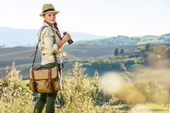 Active woman hiker hiking in Tuscany with binoculars. Discovering magical views of Tuscany. active woman hiker in hat with bag hiking in Tuscany with binoculars Royalty Free Stock Photography