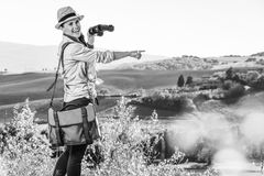 Woman hiker with binoculars in Tuscany pointing at something. Discovering magical views of Tuscany. happy healthy woman hiker in hat hiking in Tuscany with Royalty Free Stock Photography