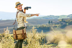 Woman hiker with binoculars in Tuscany pointing at something Royalty Free Stock Photography
