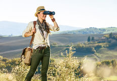 Woman hiker in Tuscany looking into distance through binoculars Stock Photos