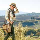 Smiling active woman hiker in hat enjoying Tuscany view Stock Image