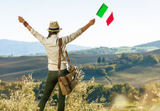 Young woman hiker on Tuscany hike with Italian flag rejoicing Stock Photo