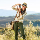 Smiling woman hiker hiking in Tuscany with retro photo camera Royalty Free Stock Photo